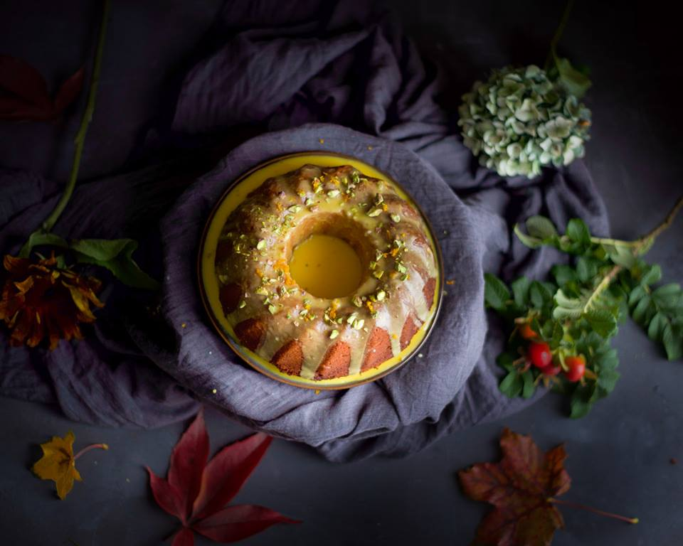 overhead view of freshly iced orange and saffron olive oil cake topped with pistachios