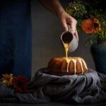 orange icing poured over orange and saffron olive oil cake
