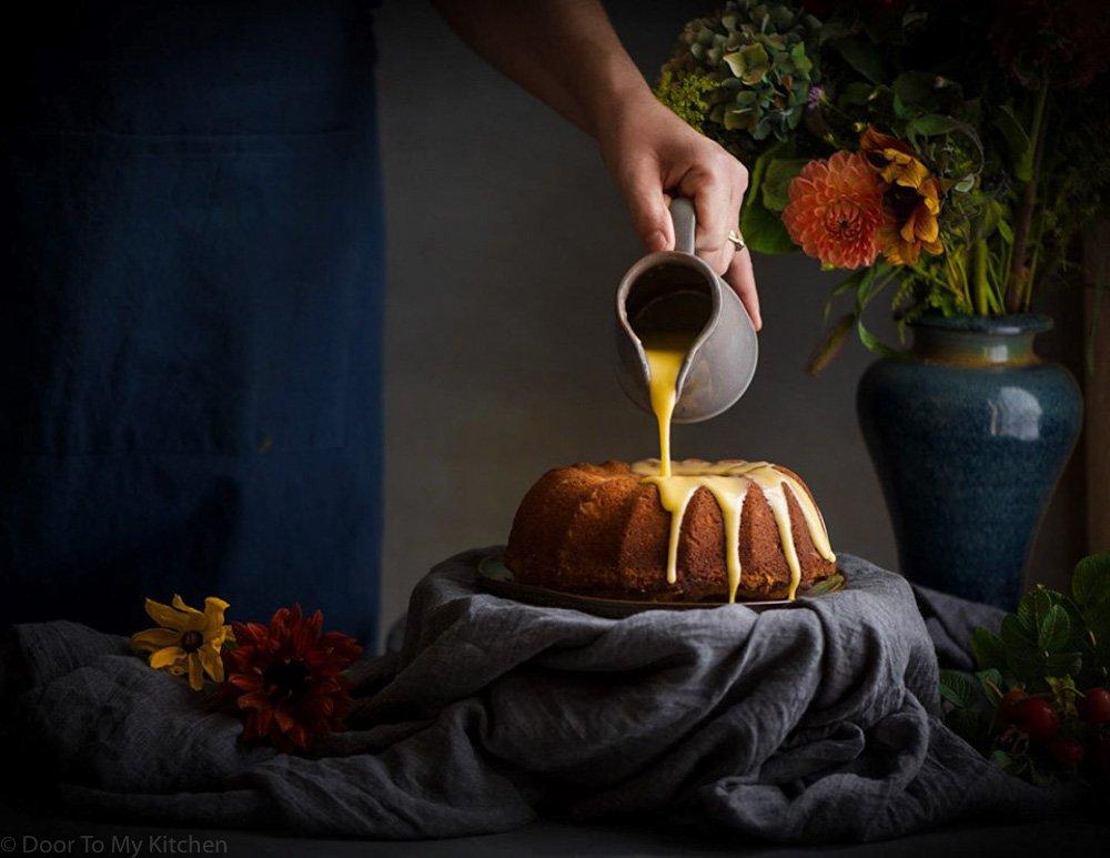 pouring orange icing over orange and saffron olive oil cake