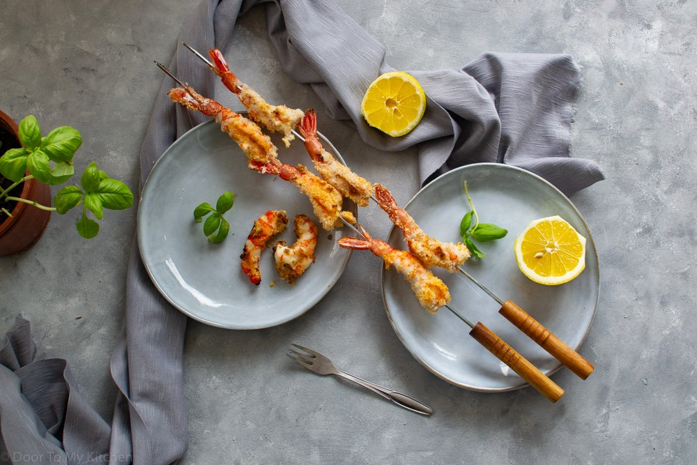 Coconut Prawns on two skiers placed on grey plates with bail and lemon