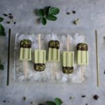 Pistachio ice cream dipped in dark chocolate and crushed pistachios on a tray of ice