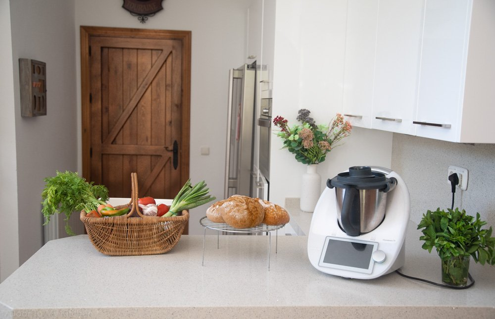 Thermomix surrounded by healthy fresh ingredients in a white kitchen
