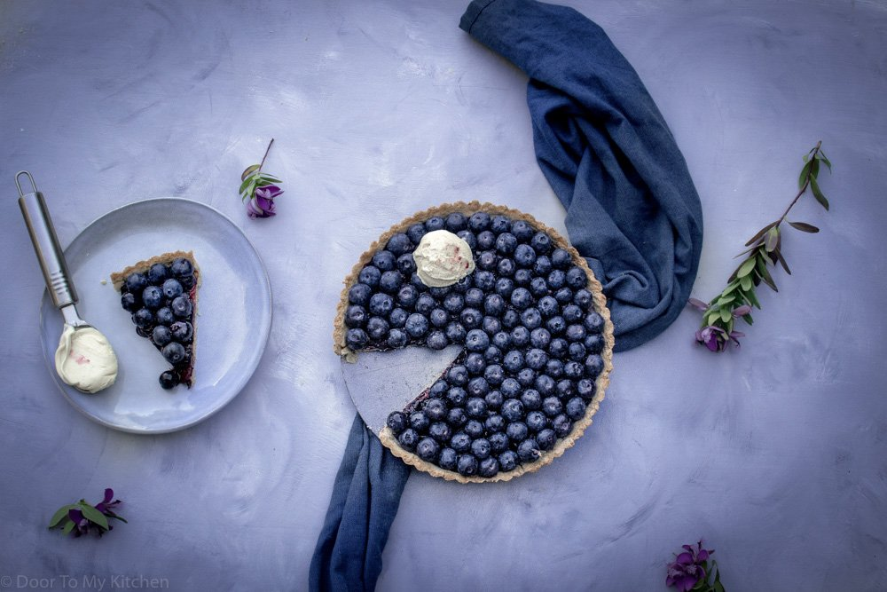 blueberry hazelnut tart with a slice missing in the tin next to a slice on a plate