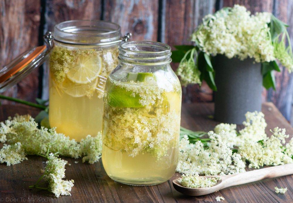 two large jars full of elderflower cordial surrounded with fresh elderflowers