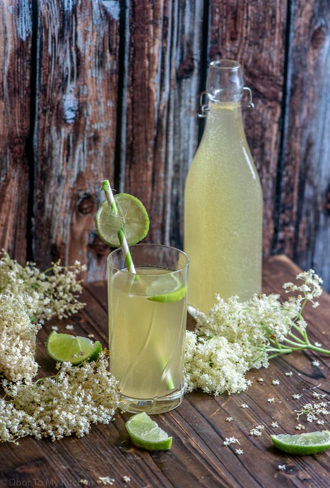 a glass ready to drink with a straw and a bottle of elderflower and lime cordial