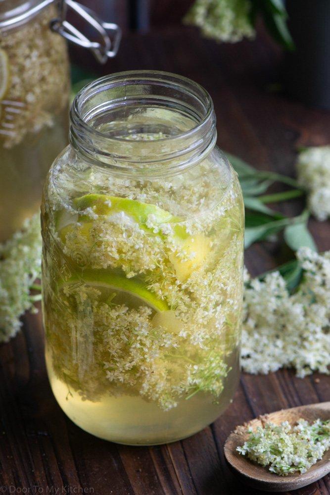 close up of making elderflower cordial with fresh elderflowers and limes