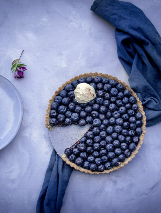 blueberry hazelnut tart in the tin topped with a scoop of vanilla ice cream