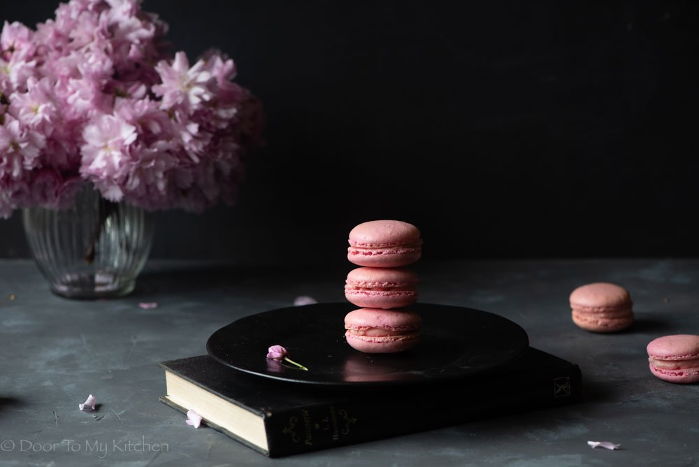 three pink macarons on top of each other on a black plate surrounded by blossoms