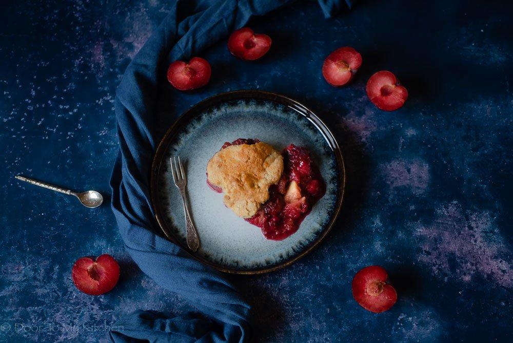 plum breakfast cobbler on blue plate with blue napkin