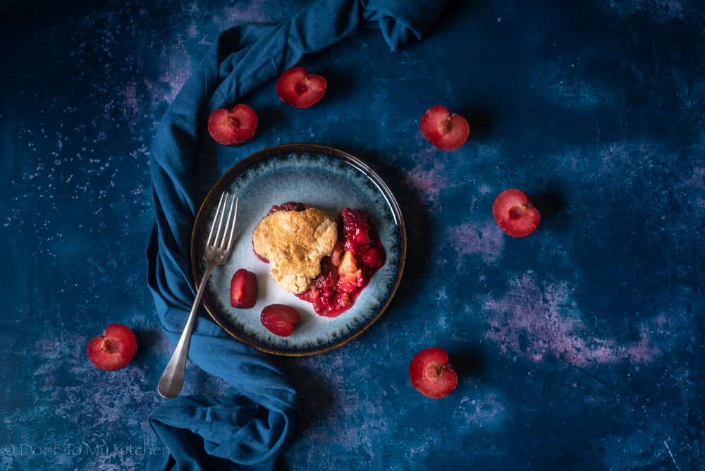 flatly of plum breakfast cobbler with plums surrounding it on a blue plate