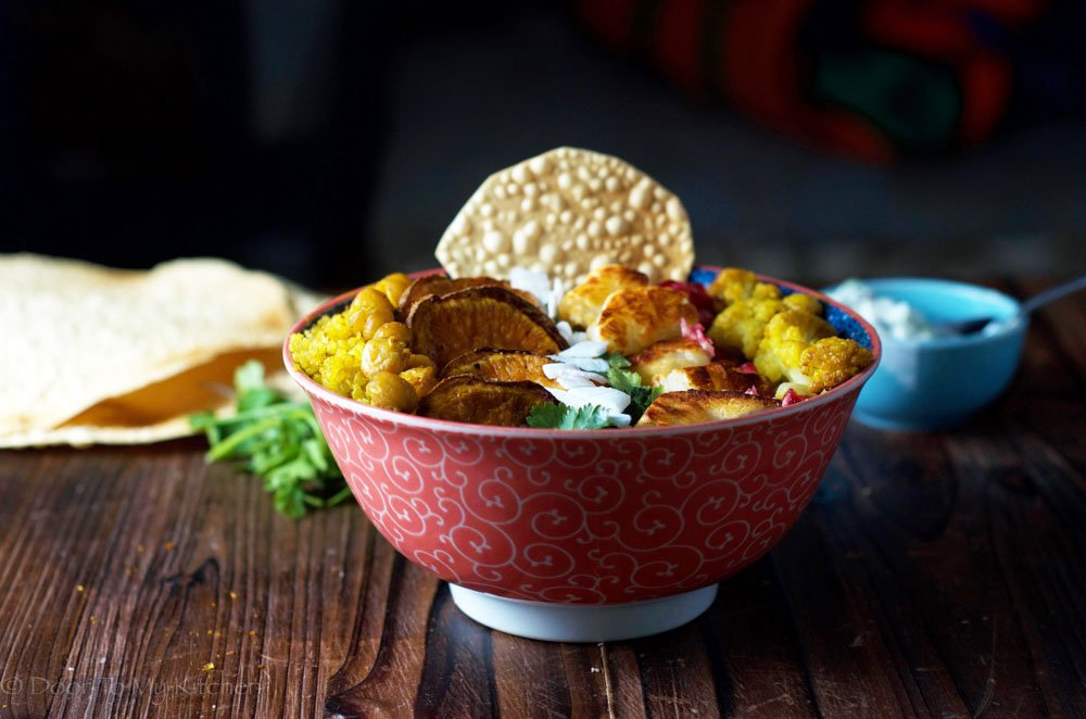 colourful buddha bowl with roasted veggies and mini poppadum topped with flaked coconut