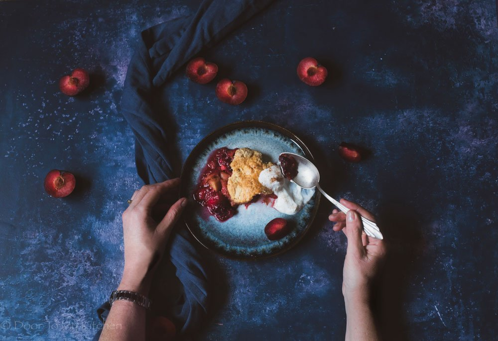Plum breakfast cobbler on a plate topped with greek yogurt and a spoon with hands displayed