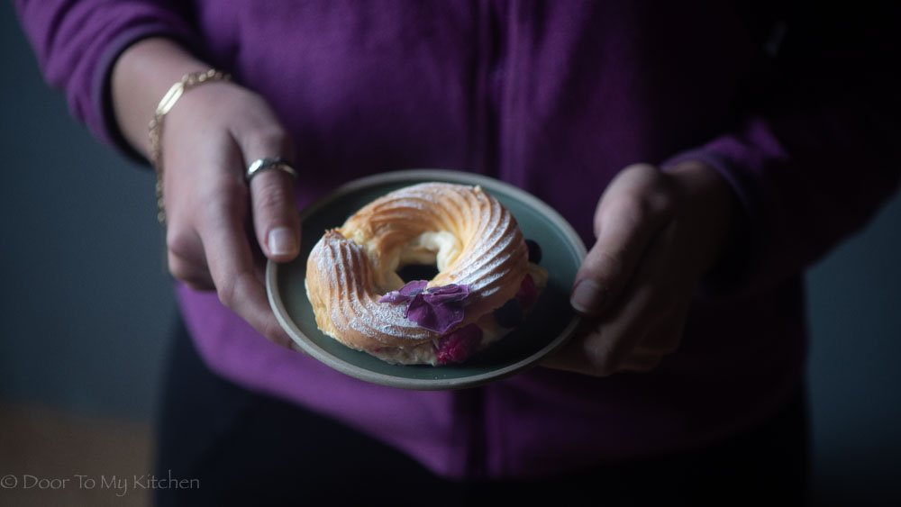 hands holding a grey plate with a berry paris brest