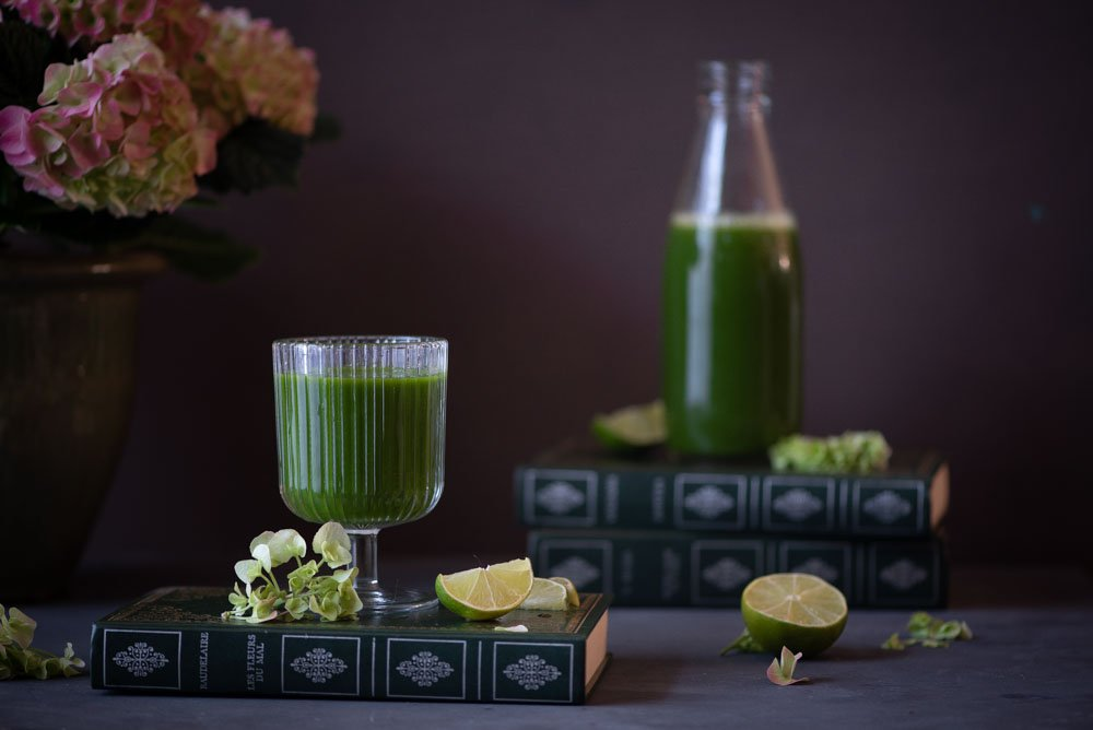 Glass of green juice with a bottle and limes