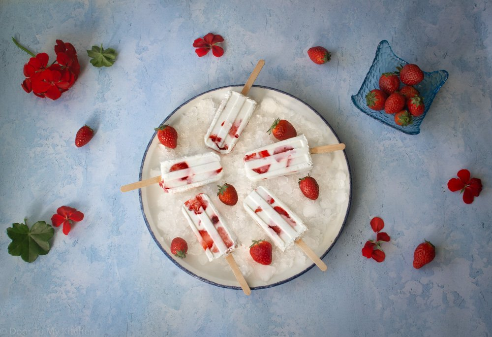 flatlay of frozen yogurt strawberry ice lollies on a plate of crushed ice surrounded by strawberries