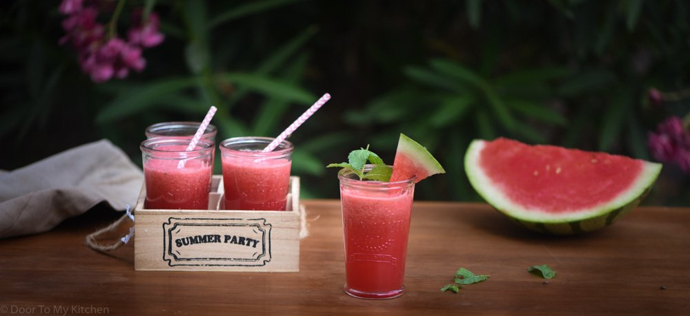 Four glasses of watermelon slushie on a table in the garden with a giant slice of watermelon