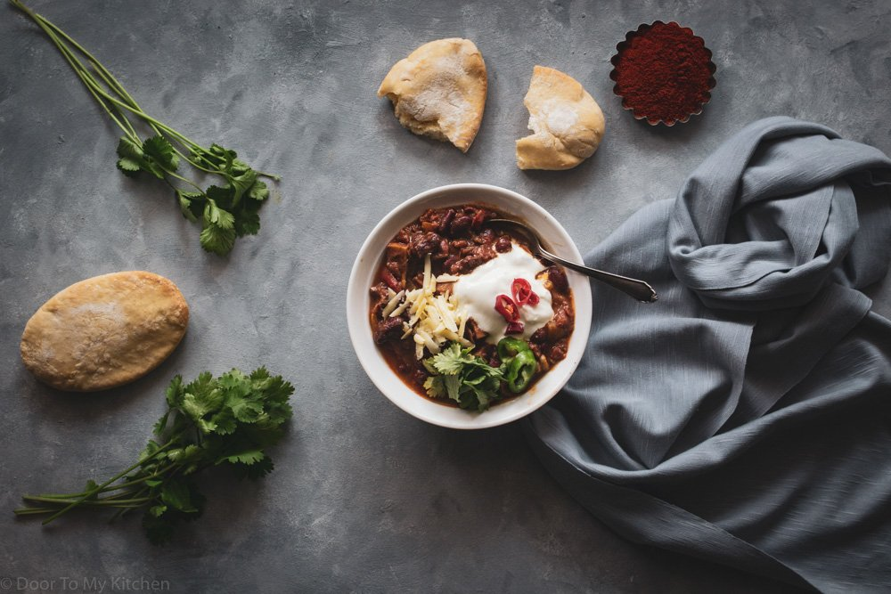 Flatlay photo of a bowl of veggie chilli with sour cream and grated cheese