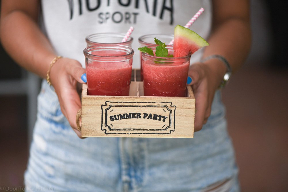 girl holding a wooden box filled with 4 glasses of watermelon smoothie with a mint sprig