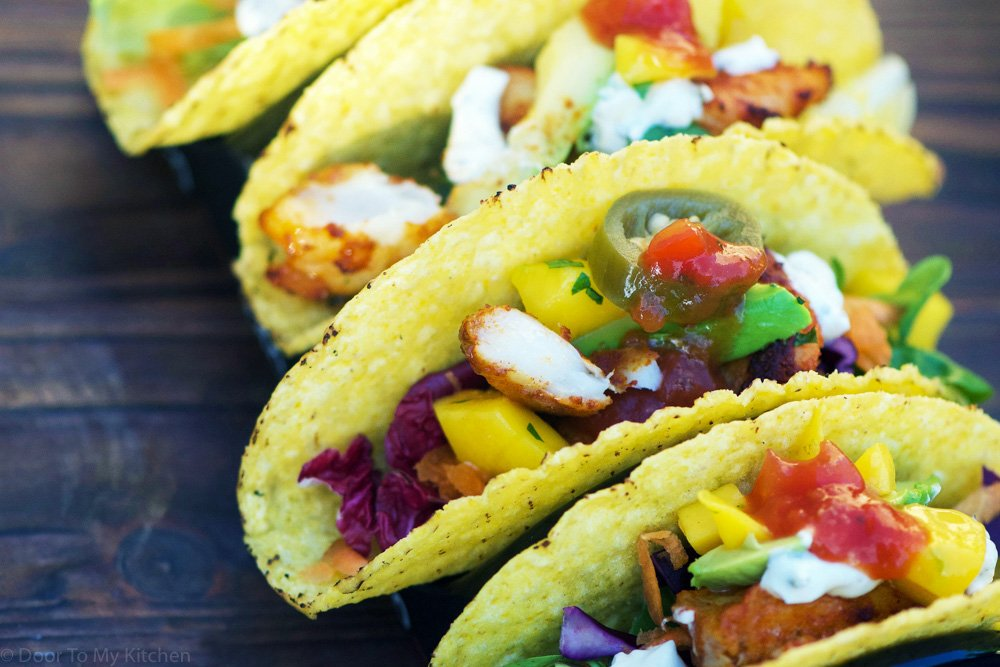 close up of tacos filled with fish, crunchy vegetables and salsa