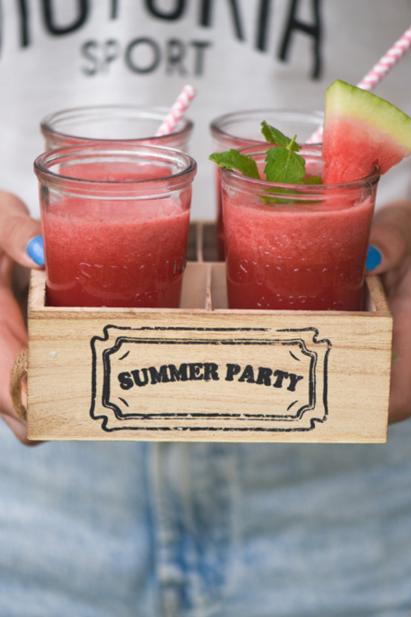 Four glasses of watermelon and mint slushie in a wooden box labelled summer party