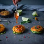 A spoon drizzling sweet chilli sauce over salmon and sweet potato cakes