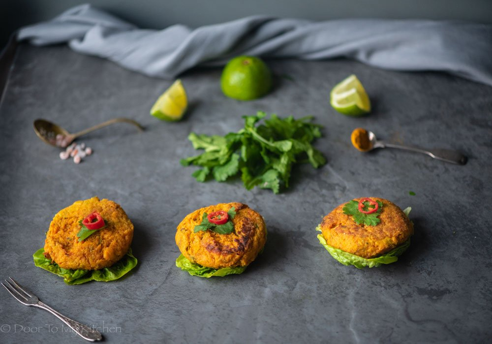 Three salmon and sweet potato cakes served on a black slate with lime and fresh coriander