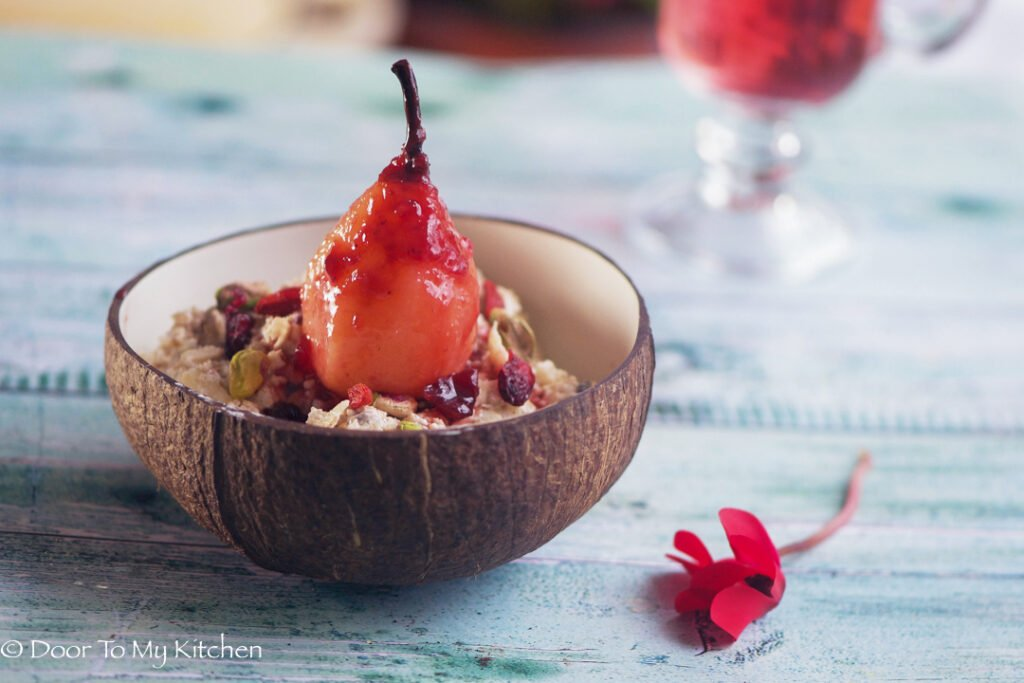 Bircher muesli in a coconut bowl topped with a sticky poached pear