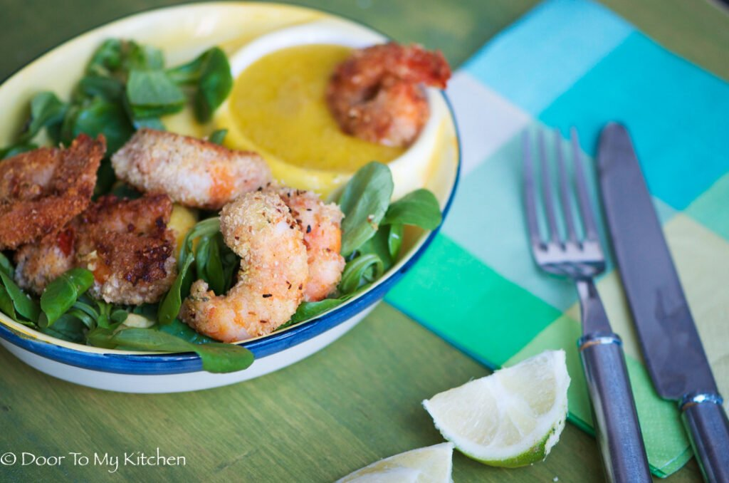 A plate of coconut prawns on salad with a mango salsa on the side