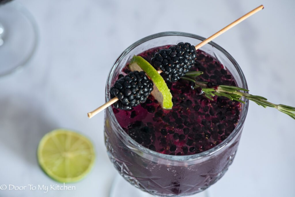 Macro overhead shot of blackberry gin fizz with garnish of lime and blackberries