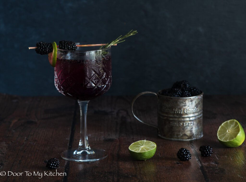 Dark and moody photo of blackberry gin fizz with a rusty cup filled with blackberries