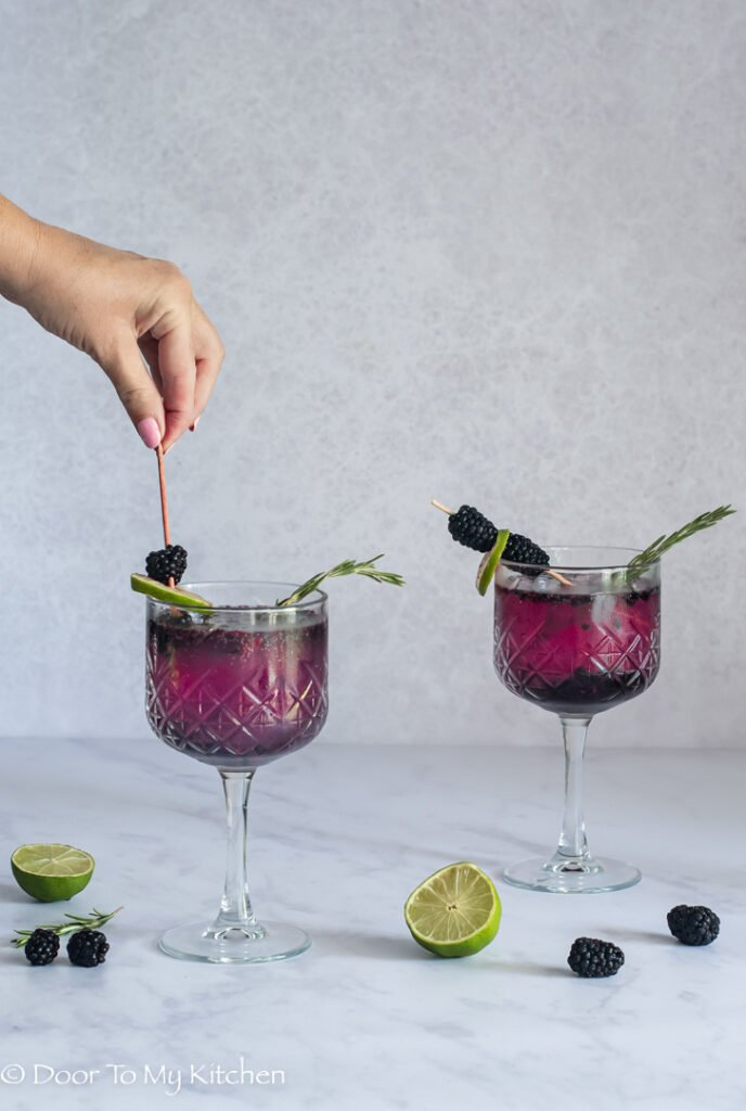 Hand stirring a blackberry gin fizz with a cocktail stick