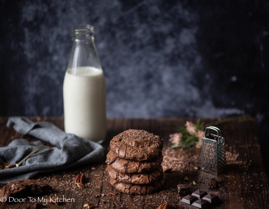 Overhead shot of a stack of chocolate brownie cookies next to grated chocolate and a bottle of milk