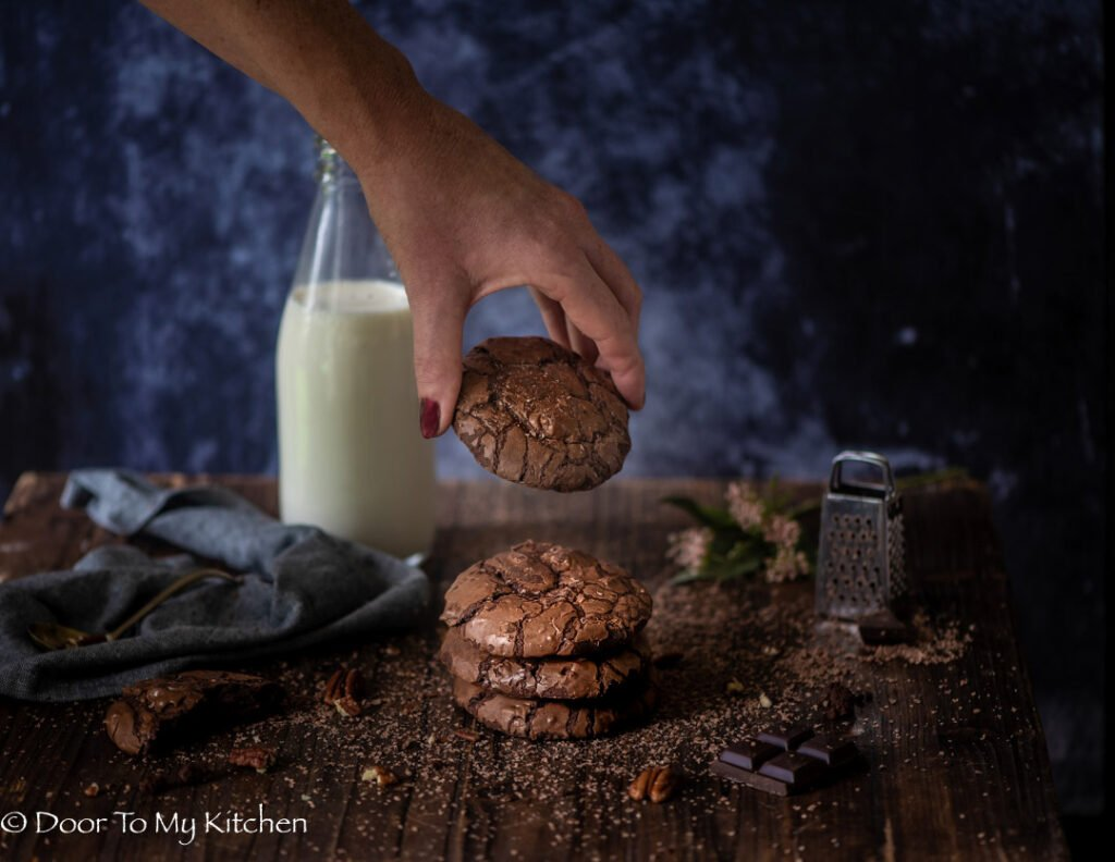 Hand reaching for a chocolate brownie cookie on top of a stack of cookies