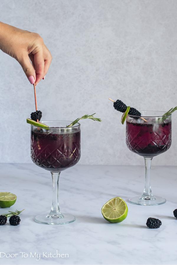 Hand mixing a blackberry gin fizz