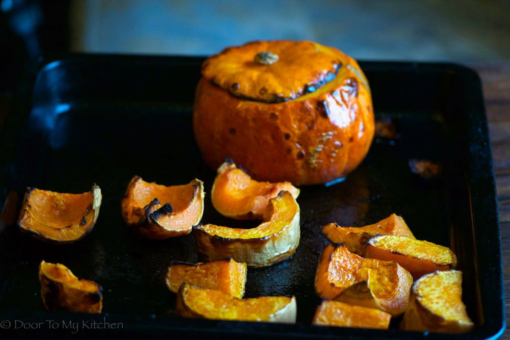 A photo of a baking tray with a whole pumpkin roasting and slices of butternut squash