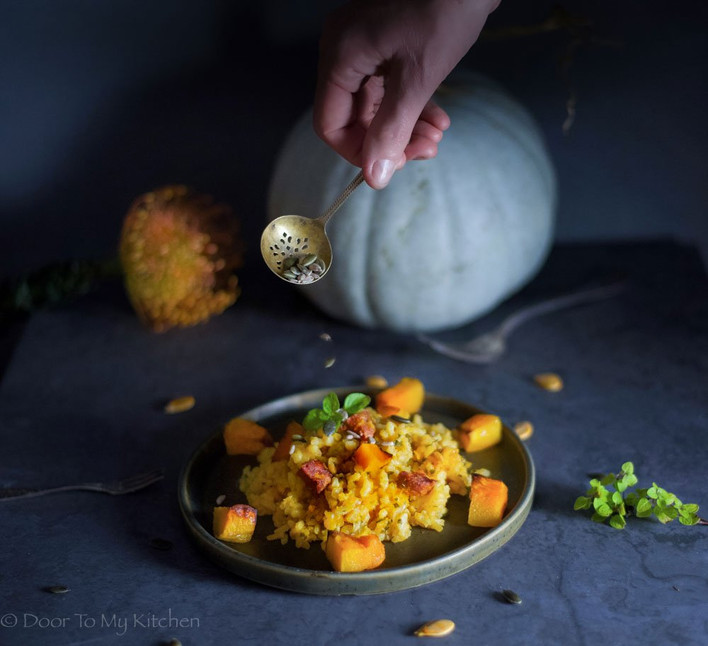 Hand sprinkling pumpkin seeds over a plate of roasted pumpkin and chorizo risotto