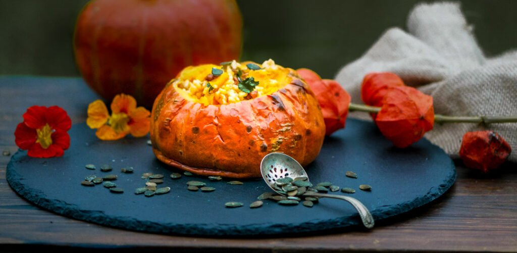 Roasted whole pumpkin filled with roasted pumpkin and chorizo risotto scattered with pumpkin seeds