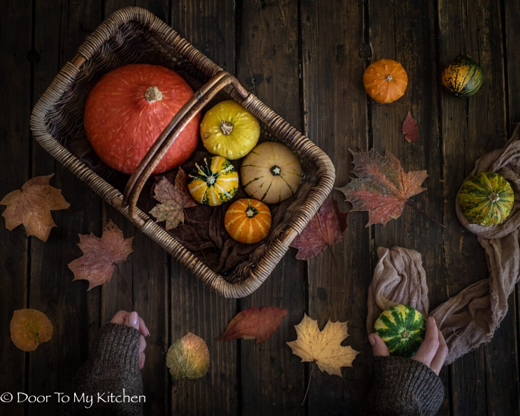 A flatlay of a basket of different sized and different coloured pumpkins with autumn leaves