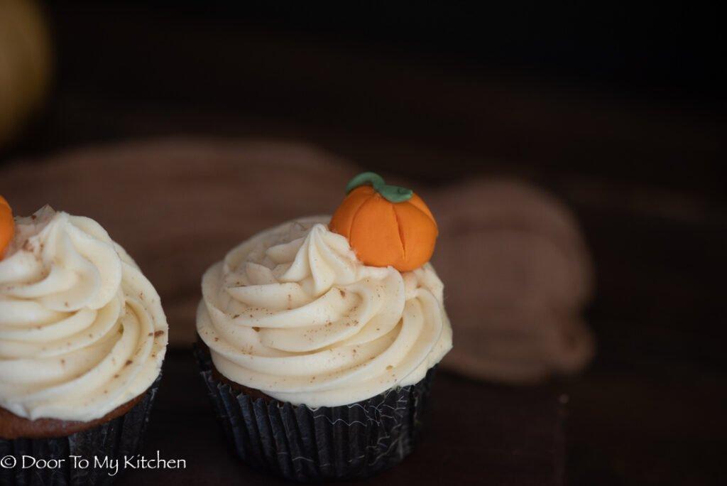 Macro shot of a pumpkin cupcake swirl with an edible pumpkin decoration
