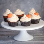 Close up of pumpkin spice cupcakes with a swirl of icing and pumpkin decoration