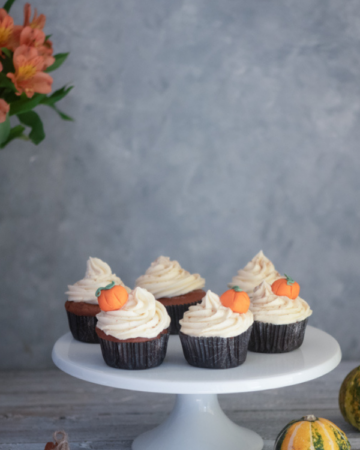 Pumpkin spice cupcakes on a white cake plate