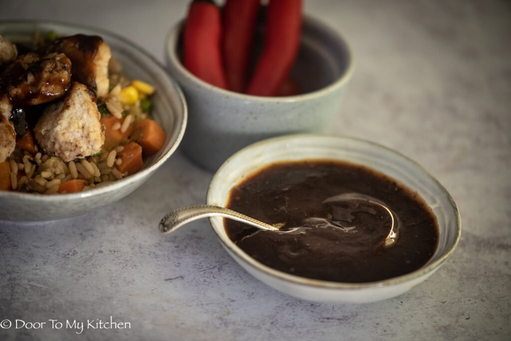 Close up shot of a grey bowl with hoisin sauce next to Chinese chicken and a bowl of chillies