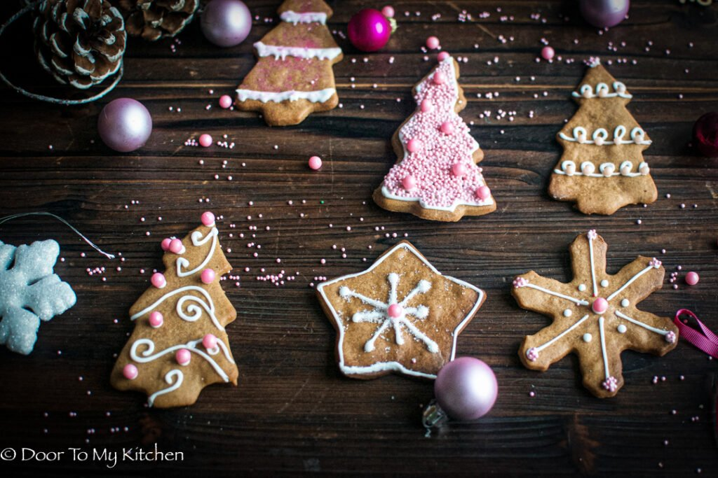 Flatlay of Gingerbread cookies iced with pink decorations surrounded by fairy lights