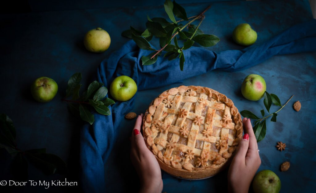 Two hands around an entire latticed caramel apple pie with apples and apple leaves on a dark blue background