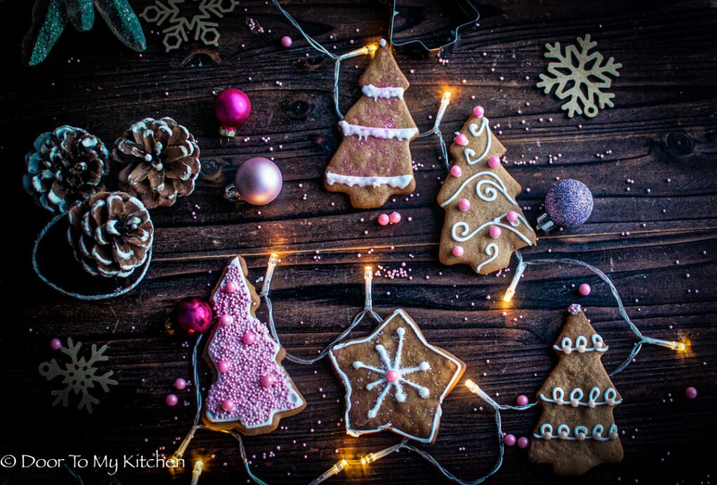 A selection of iced Christmas cookies decorated with pink with fairy lights and pink baubles