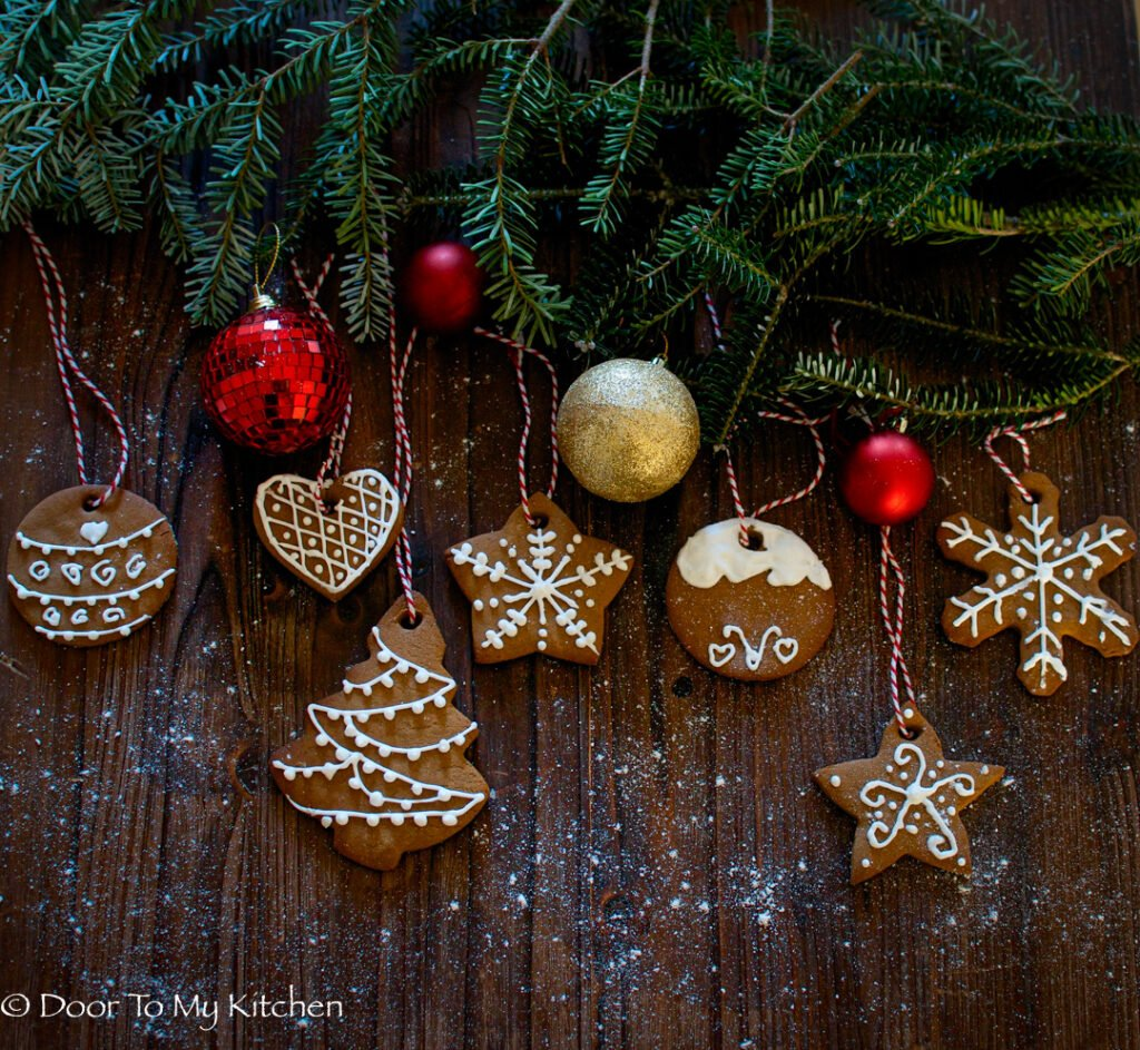 Arty shot of some for tree leaves with baubles and cookies hanging down on festive string
