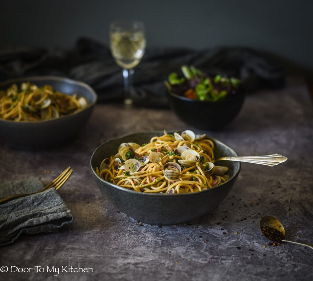 Rustic bowl of spaghetti with clams and a glass of white wine