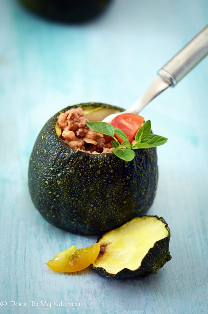 A round courgette stuffed with minced lamb on a blue background