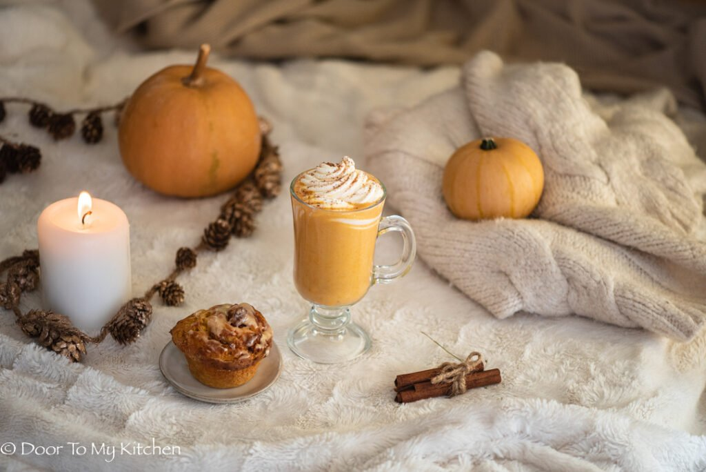A hygge scene with a fluffy blanket, pumpkin spice latte, cinnamon bun, pumpkins and candle
