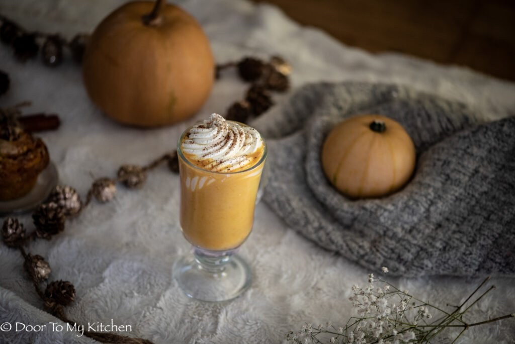 Pumpkin spice latte on a fluffy blanket with jumper and pumpkins